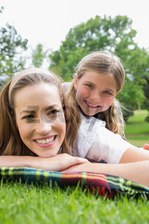 Happy mother with daughter lying at park