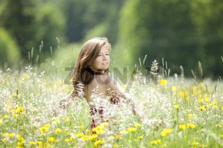 Junge Frau tanzt in einer Blumenwiese