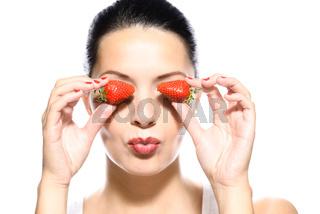 Schöne junge Frau hält Erdbeeren an ihre Augen