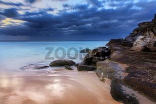 Stunning beach and coastal rocks before sunrise