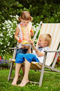 Kinder teilen frisches Obst im Garten