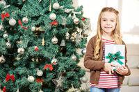 Kind mit Geschenk neben Weihnachtsbaum zu Weihnachten