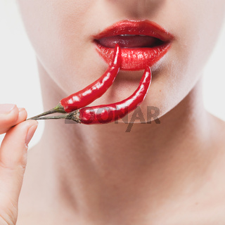 Young woman with chili pepper isolated on white
