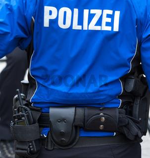 Streifenpolizei mit Einsatzgurt von hinten