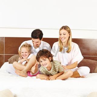 Lachende Familie mit Kindern auf Bett
