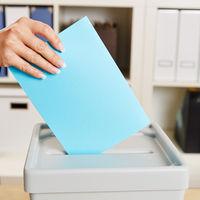 Hand mit Stimmzettel bei Wahlen