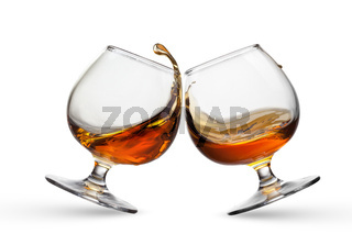 Splash of cognac in two glasses isolated on white background