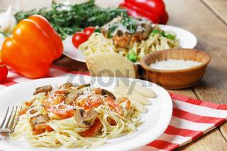 Pasta with shrimps and mashrooms on the wooden table