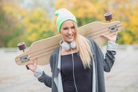 Happy young woman carrying a skate board