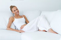 Happy Sexy Woman Leaning at White Couch