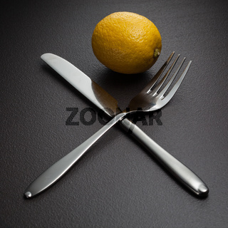 lemon with crossed knife and fork on black