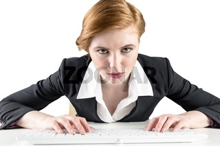 Redhead businesswoman sitting at desk typing