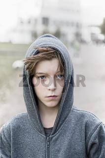 portrait of a teenage boy with grey hoodie sweatshirts
