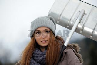 Junge Frau mit Schneeschaufel