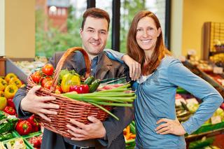 Zufriedenes Paar mit Gemüse im Biomarkt