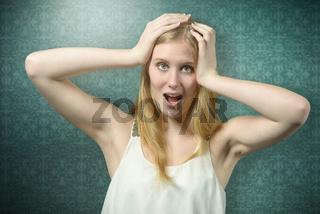Schockierte junge Frau hält die Hände an den Kopf
