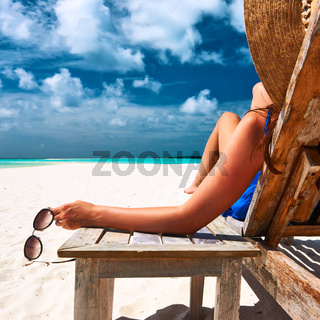 Woman at beach holding sunglasses