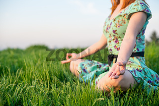 Pretty woman meditate in the park