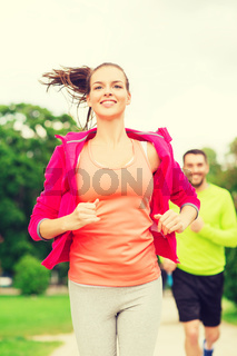 smiling couple running outdoors