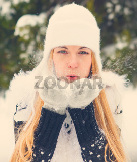 Beautiful woman blowing snow outdoors