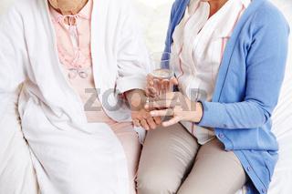 Seniorin bekommt Medizin in die Hand