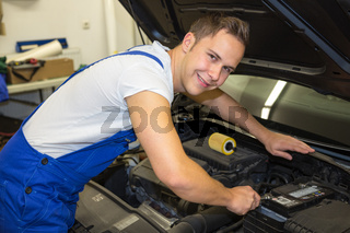 Mechanic with tools in garage repairing the motor of a car