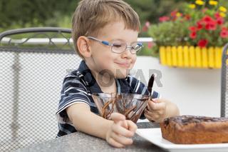 Little boy decorating the chocolate cake