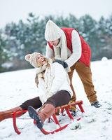 Mann schiebt Frau auf Schlitten im Schnee