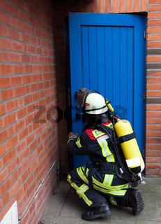 Feuerwehrmann oeffnet eine Tuer im Einsatz