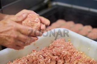 Koch formt Frikadelle mit der Hand