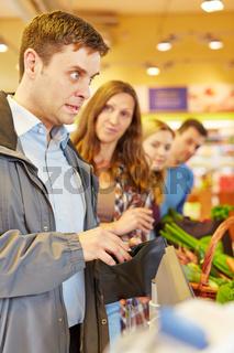 Mann an Kasse vom Supermarkt hat Geld vergessen