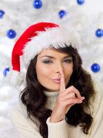 Woman in Santa hat making a shushing gesture