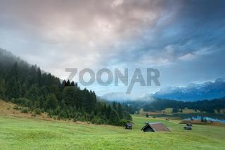 misty sunrise over alpine meadows by Geroldsee lake