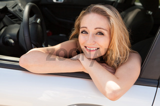young attractive happy woman sitting in car summertime