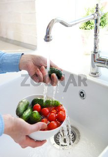 Cropped image of woman washing tomatoes and cucumbers at the kitchen