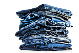 Stack of blue jeans on white