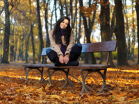 Woman in Autumn Fashion Sitting on Bench