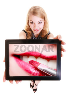 Girl showing tablet with lips lipstick. Makeup.