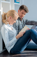 Young Couple Sitting on Floor Reading Book
