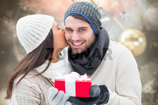 Composite image of winter couple holding gift