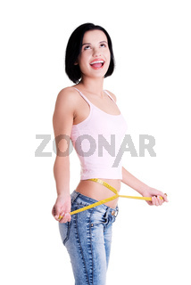 Happy young woman measuring her waist