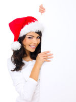Cute woman wearing Santa hat with a blank sign