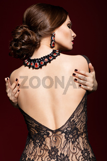 Young beautiful woman in black dress from back side on marsala color background