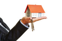 Hand hält Haus mit Schlüssel