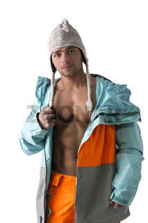 Attractive young male skier or snowboarder with open coat on naked muscular torso