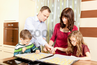 Family baking Christmas cookies in the kitchen
