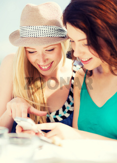 girls looking at smartphone in cafe