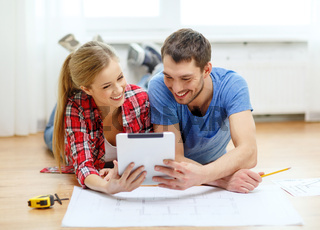 smiling couple looking at tablet pc at home