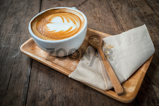 Cup of cappuccino coffee on wooden plate and brown sugar in spoon. Food background in vintage style
