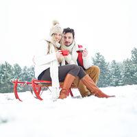 Paar im Winter auf Schlitten trinkt Tee